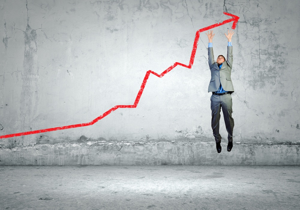 Image of young businessman jumping above graph.jpeg