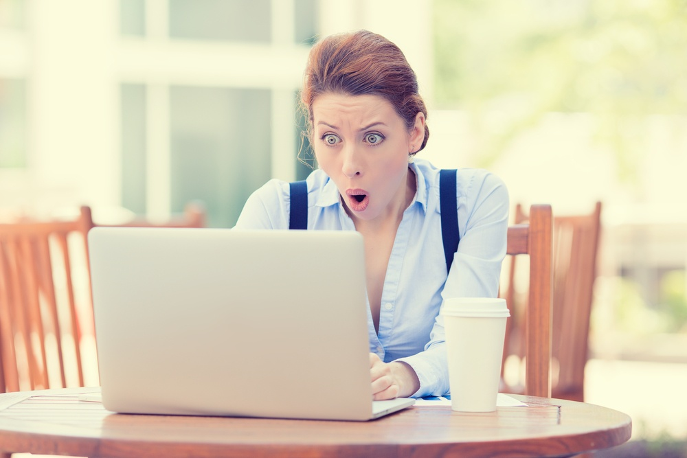 Shocked young business woman using laptop looking at computer screen blown away in stupor sitting outside corporate office. Human face expression, emotion, feeling, perception, body language, reaction-1.jpeg
