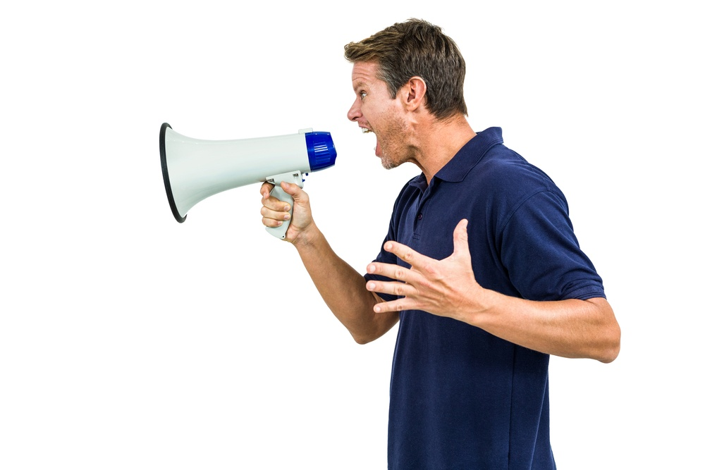 Side view of angry man shouting through megaphone against white background.jpeg