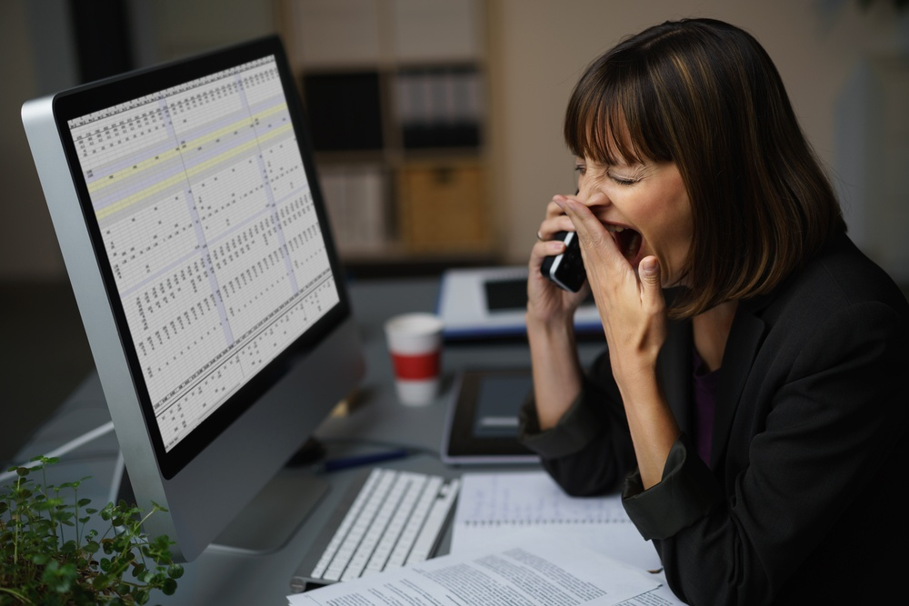 Tired Businessman at her Desk, Showing Yawning Gesture While Talking to Someone on Mobile Phone..jpeg