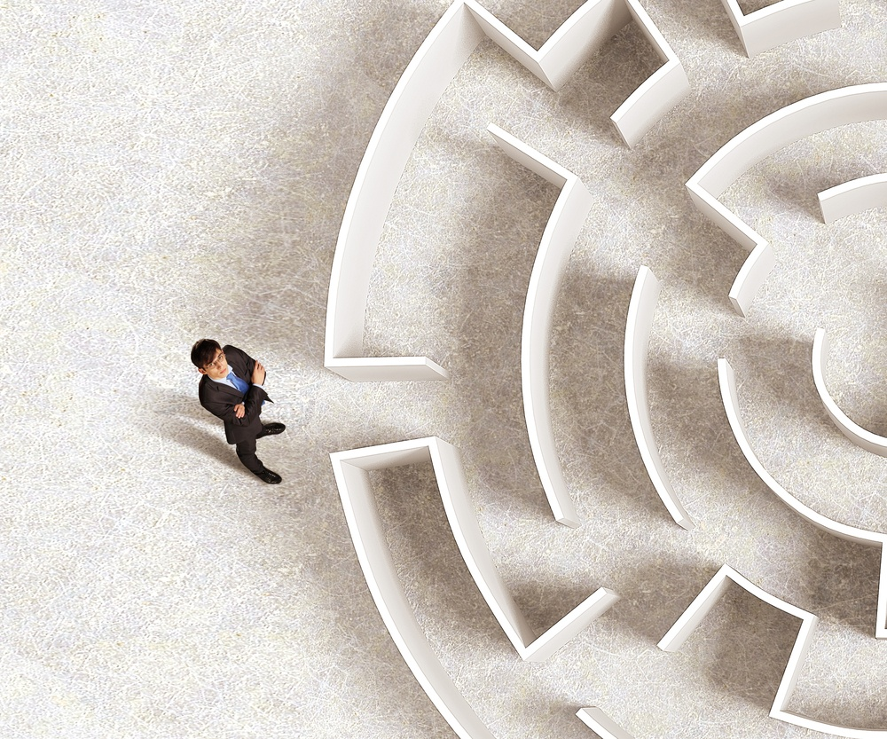 Top view of successful businessman standing near the entrance of labyrinth.jpeg